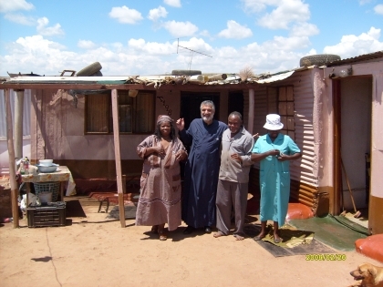 Beauty Ndlovue, Fr Athos, Obed Khumalo and visitor outside their home in Atteridgeville.