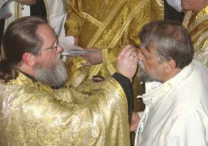 Orthodox priest anointing the sick