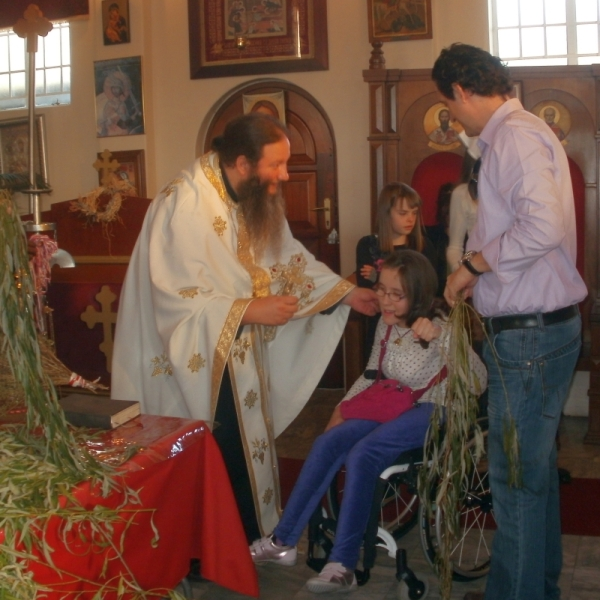 Children receiving bells and willwo branches