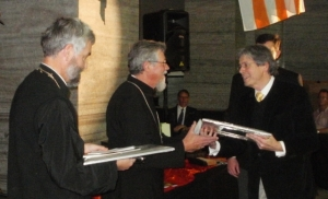 Danie Goosen presents the award to Fr Zacharias van Wyk while Fr Kobus looks on