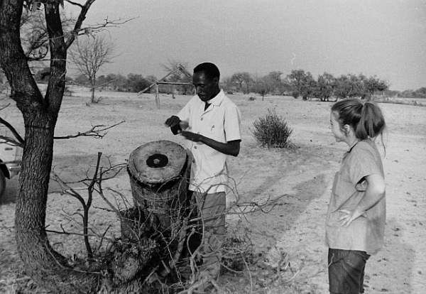 Toni Halberstadt watches as Fr Lazarus Haukongo shows how a drum is used to tell people about church srervices