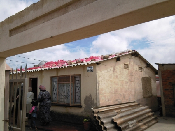 Christina Mothapo's house, with plastic bags on the roof, to try to block the holes smashed through by the hailstones.