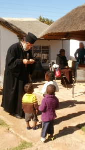 Archbishop Damaskinos giving ikon cards to some of the children who were at the service