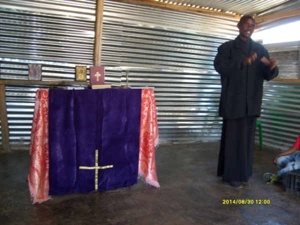 Father Markos speaking to the congregation at Madidi.