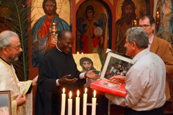 Azar Jammine, a former chairman of the parish council, presents a gift to Fr Athanasius, while Fr George Coconos and Stephen Reynders look on (Photo by Jethro Hayes)