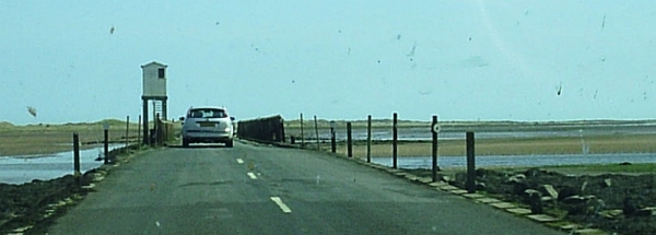 The causeway to Holy Island. The causeway can only be used at low tide, and the poles at the side of the road show where the high tide reaches, to indicate when it is unsafe to cross.