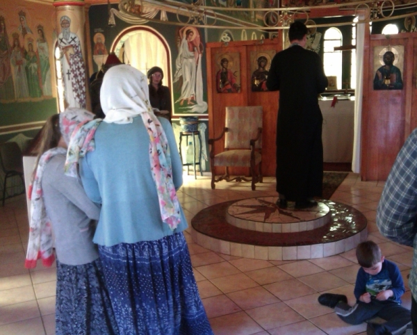 Fr Elias leading the Akathis hymn. In the foreground, in isishweshwe skirts, are Angela and Martha Krunic.