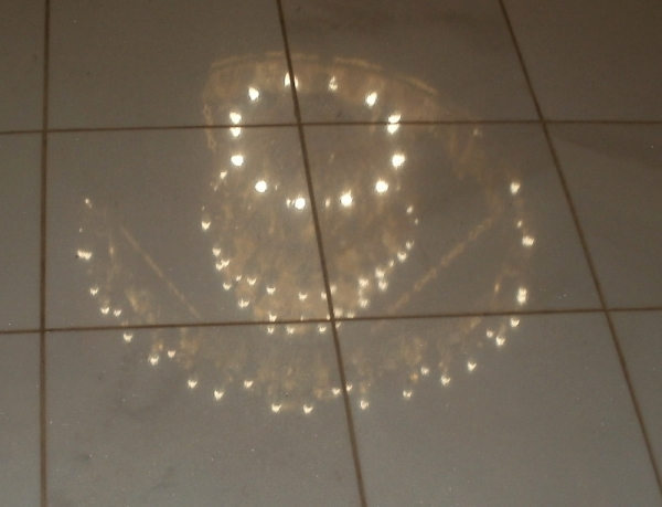 The church chandelier reflected in the floor tiles